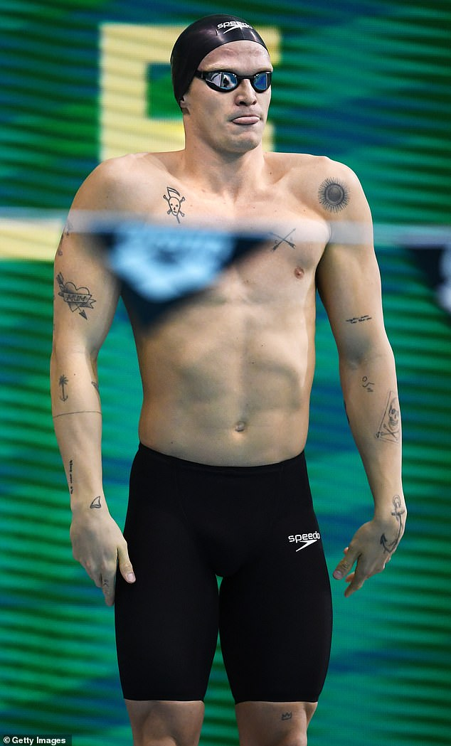 Ready for the race: The tattooed crooner finished off his running outfit with a black swim cap and matching goggles