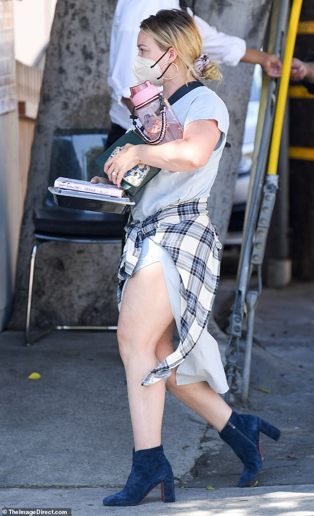 On the go: The Lizzie McGuire alum stepped out in dark blue ankle boots. She tied her hair back from her face with a scrunchie and wore a face mask and large gold hoop earrings