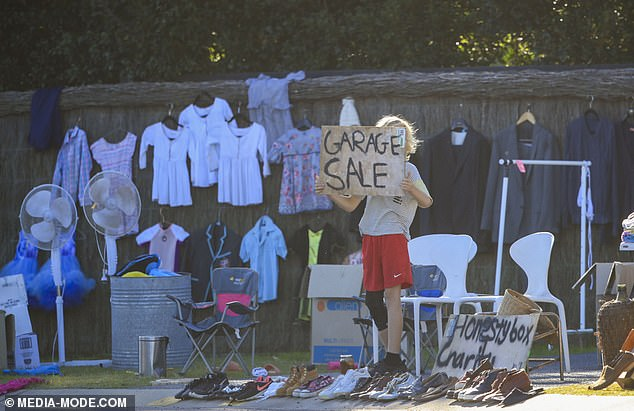 Helping Hand: One of the chef's sons was also seen holding a 'garage sale' sign