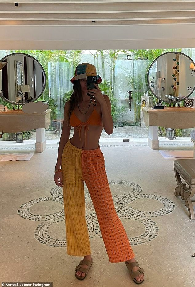 Look finished: Before boarding the boat, she captured a selfie in a mirror that showcased her bright orange bikini top and contrasting color pants.