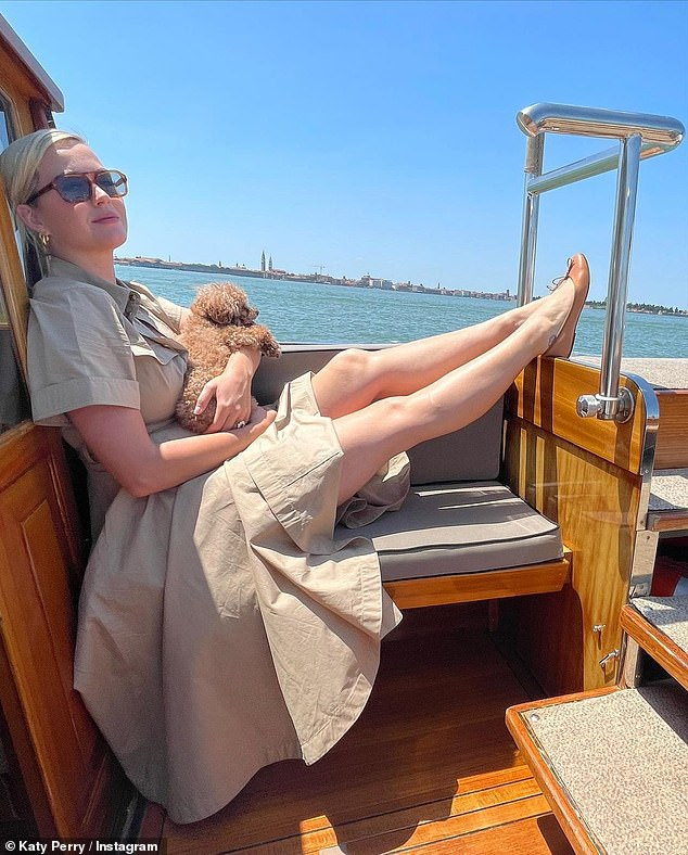 Baby in fur: Katy also shared a gorgeous photo of herself enjoying a boat ride in an elegant beige dress while her beloved pet dog Nugget sat on her lap