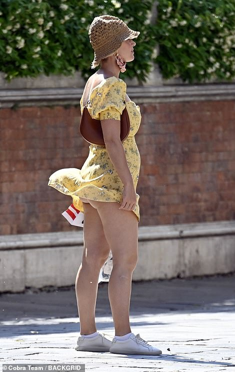 Some like it hot?  Katy, 36, inadvertently imitated Marilyn Monroe, right, on a walk along the canal as her yellow floral summer minidress caught the breeze, the singer having to adjust it before showing off her underwear. clothing
