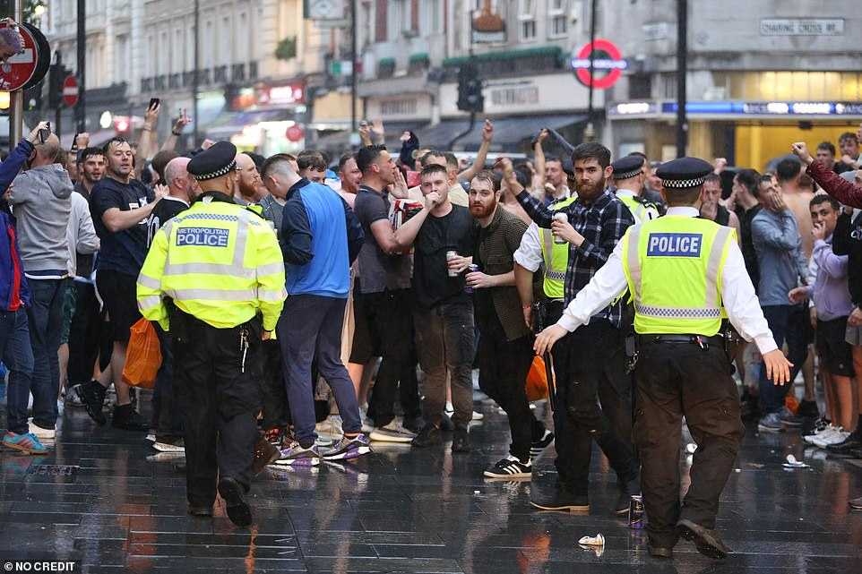 Police on patrol in Leicester Square as Scotland football fans sing and drink in the rain in central London on Thursday evening