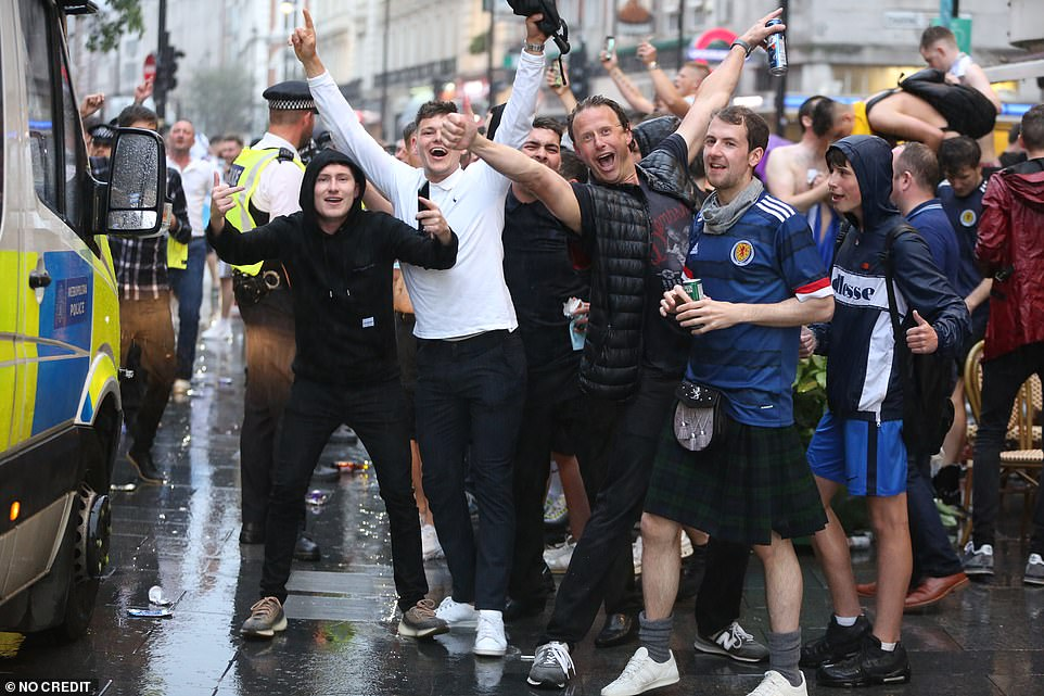Scotland football fans party in Leicester Square last night amid the pouring rain ahead of the Uefa clash with England