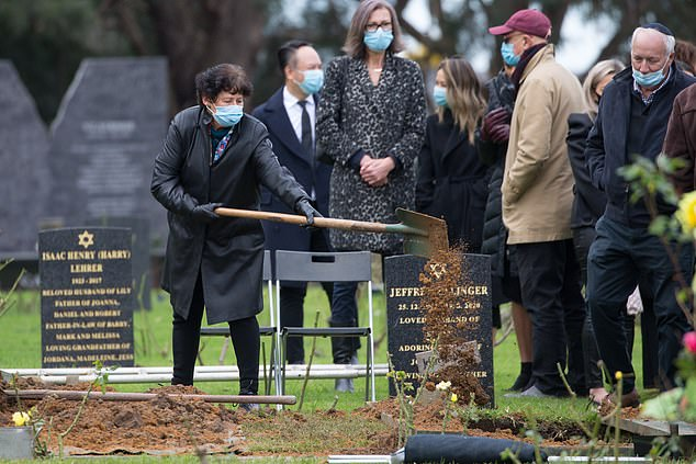 Mourners toss dirt on the casket of Geoffrey Edelsten at his funeral on Wednesday