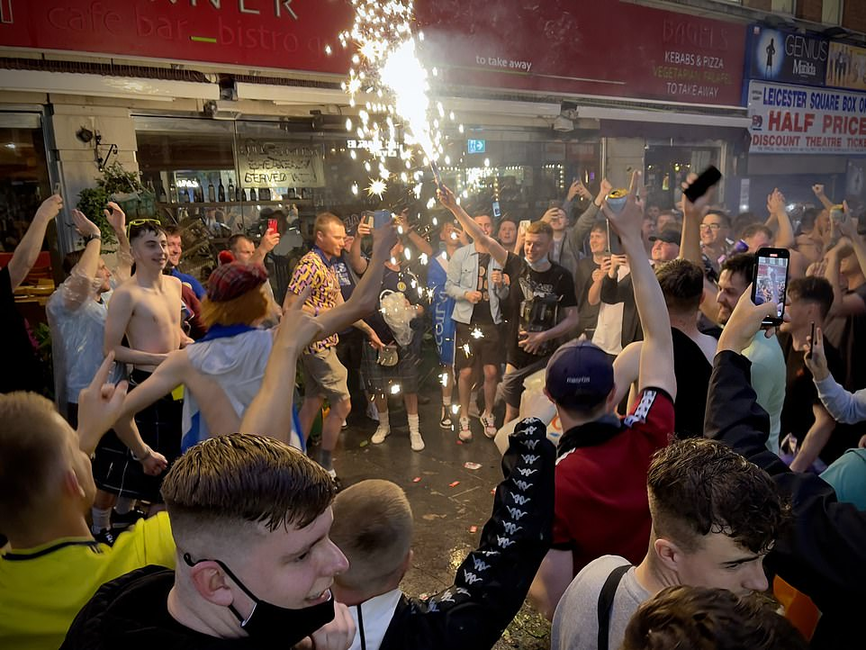 Scotland football supporters light flares in Leicester Square, central London, ahead of the Uefa clash last night