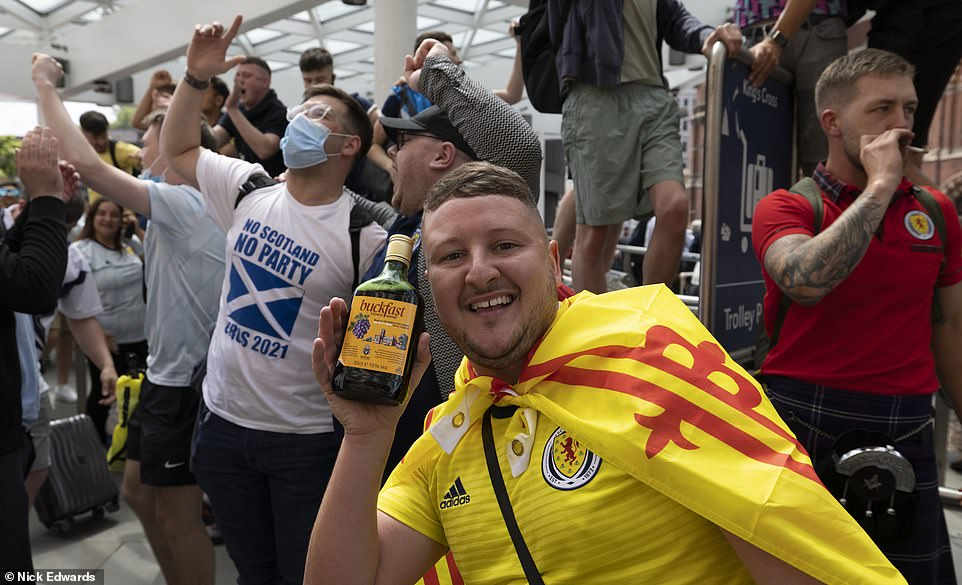 Scottish football supporters - one clutching a bottle of Buckfast - look jovial as they wait in King's Cross Station yesterday