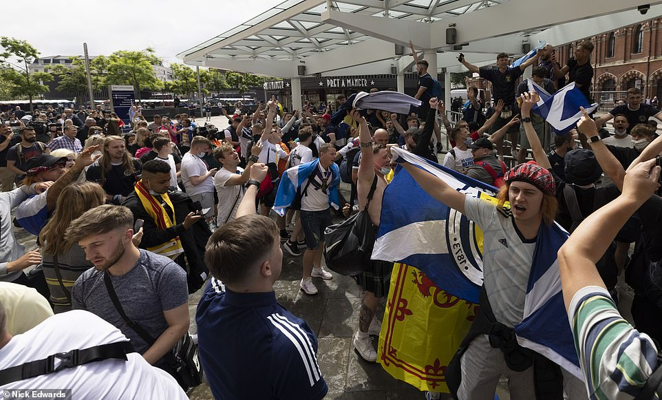 Football supporters are seen cheering and chanting outside King's Cross Station yesterday in central London