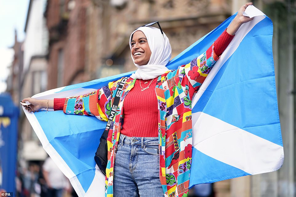 A Scotland fan at Central station in Glasgow yesterday as she prepares to travel to London ahead of the Uefa clash