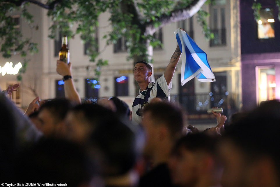 One fan was seen waving a flag in the air last night as others clutched beer amid celebrations ahead of the England match