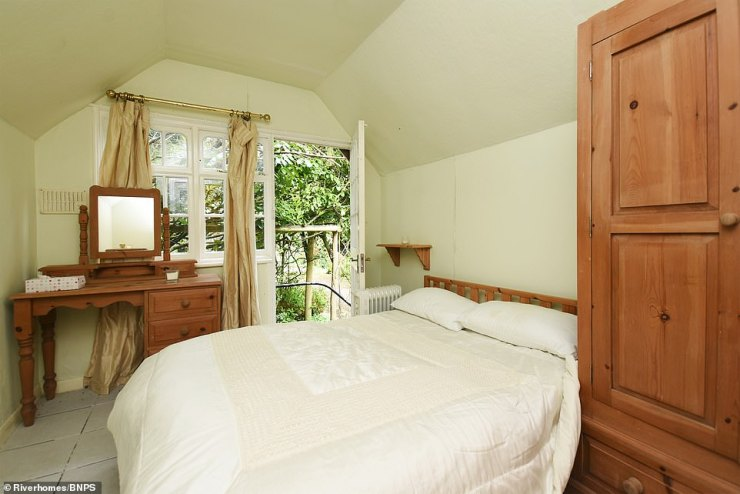 Pictured: Another of the property's bedrooms which features a side door with access to the garden and moorings on the home's site