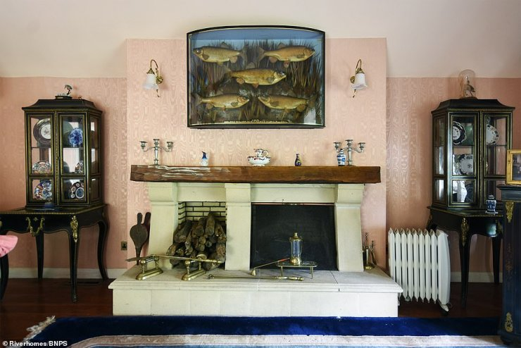 Upstairs it has two bedrooms, a large reception room overlooking the river, a galley kitchen and a bathroom.Pictured: The living room with ornate wallpaper and a log fireplace