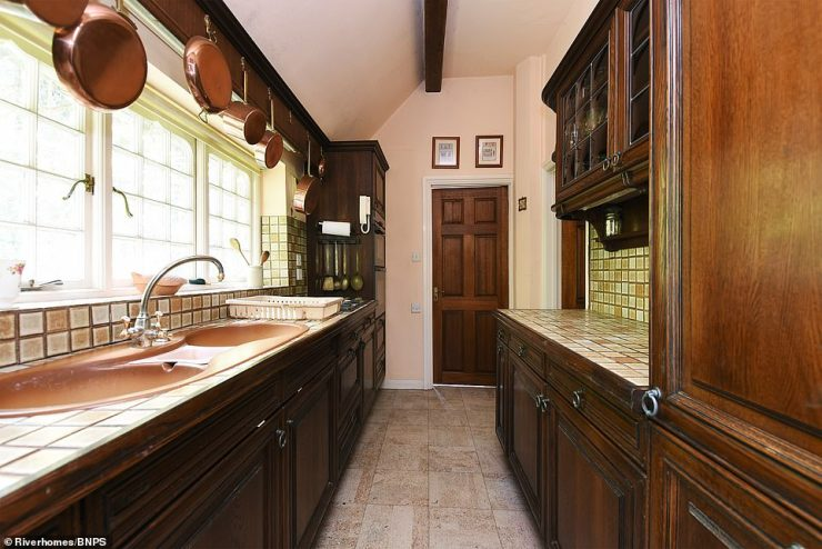 The kitchen of the Victoria property features more exposed brick and boasts stone floors and bay windows with metal handles