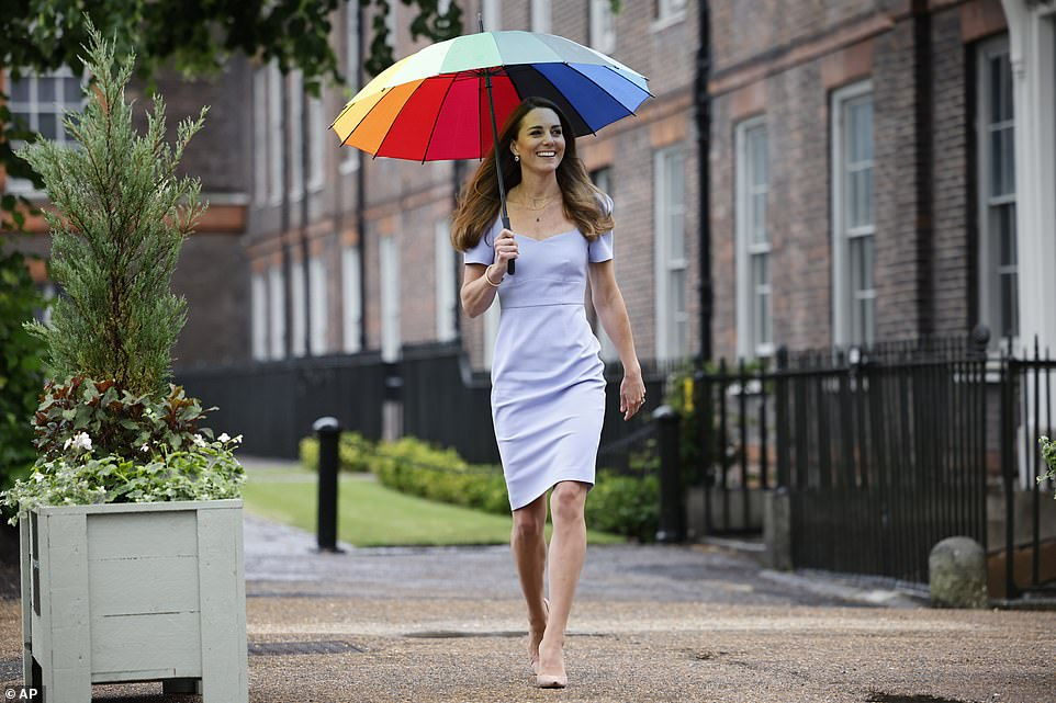 As Prince William spoke out to deny the Royal Family is racist, the Duchess of Cambridge was seen sheltering from the rain with a vibrant rainbow umbrella as she arrived at Kensington Palace for an event on Friday