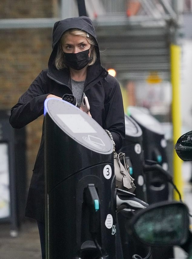 Soggy: The presenter, 40, stepped out in a gray t-shirt and black face mask as she bundled up in an attempt to stay dry