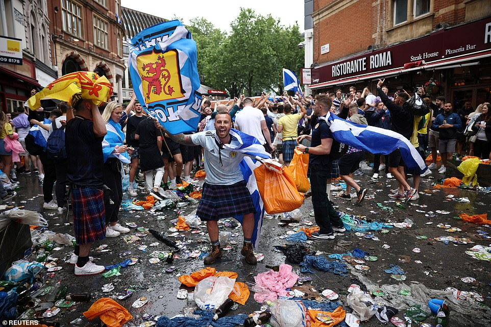 Supporters dance among the litter in central London after thousands of fans descended for the Euro 2020 clash between the old rivals