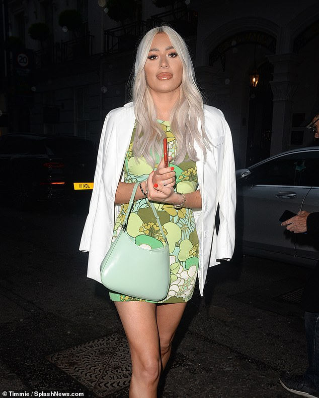 Stylish: Demi kept off the chill by draping a while blazer around her shoulders and completed the outfit with a silver bangle and matching watch