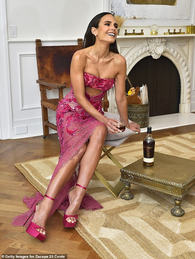 Stunner: She stood tall in magenta platform stilettos and had her lustrous raven locks swept back pin straight