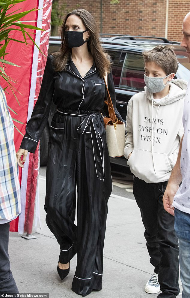 Dining out: Angelina Jolie stunned in a silky black jumpsuit as she spent some quality time with her sons Pax, 17, and 12-year-old Knox at a ramen hotspot in New York City on Friday