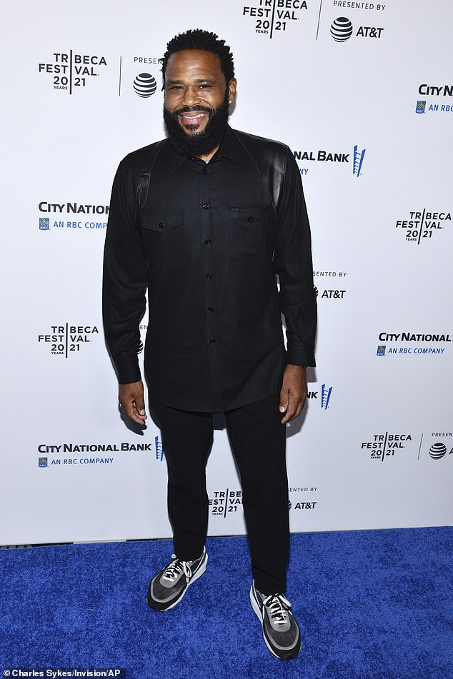 Stylish: Anderson wore an all-black ensemble with a holster over his shoulders