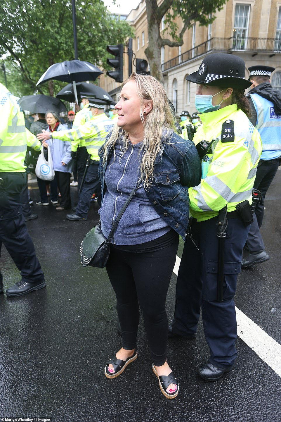 Eight arrests were made onBridge Street, Westminster, where a crowd blocked a road. A woman is seen being detained by a police officer