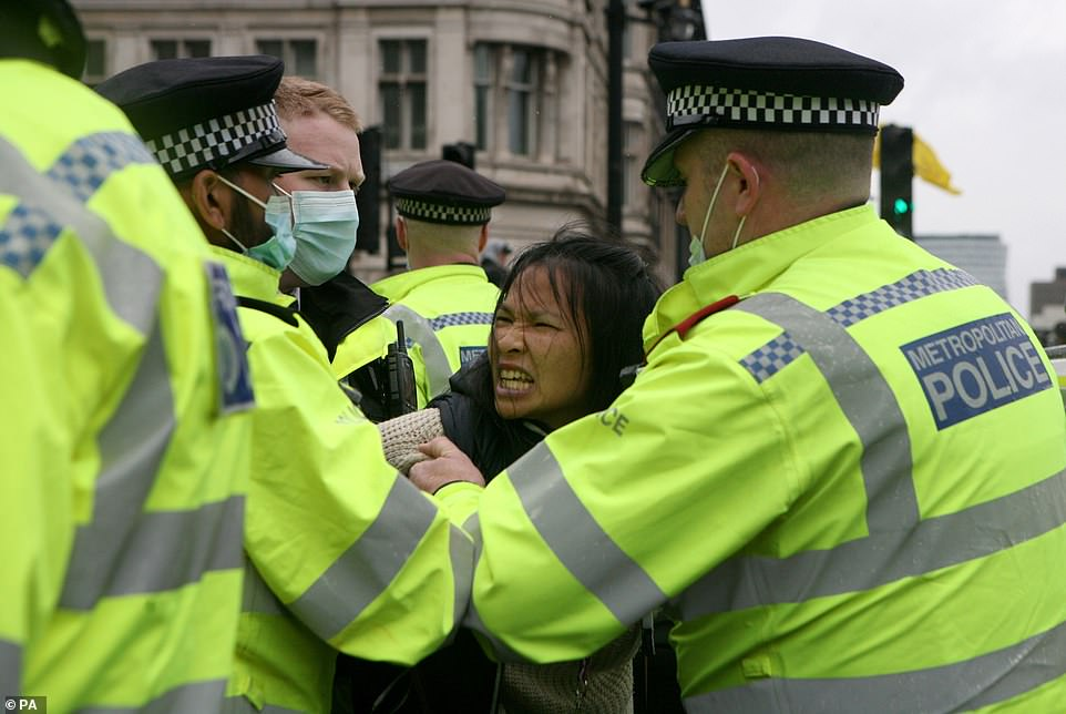 Police confirmed they have arrested 14 people who were 'obstructing' roads and being 'hostile to officers' as they attempted to contain a large group of Covid sceptics in Parliament Square and on Whitehall - on what would have been the day social distancing measures were lifted across the UK