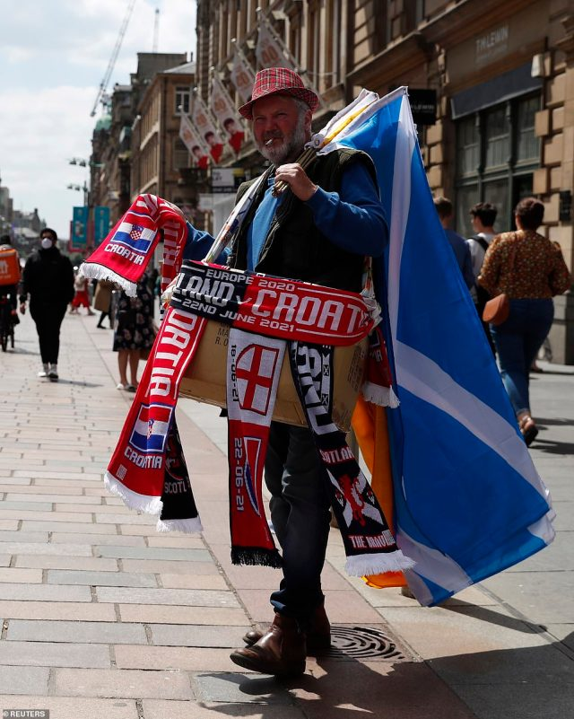 A merchandise seller is pictured in Glasgow ahead of the match tonight, selling scarves and flags to passers-by