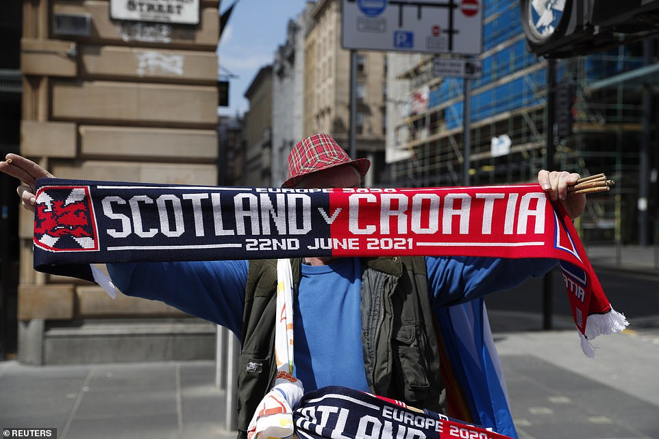 A merchandise seller is seen in Glasgow this afternoon ahead of the match which takes place at Hampden Park at 8pm