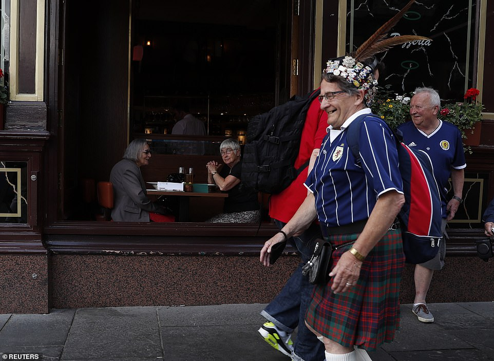 Scotland fans smile as they walk through the city wearing kilts ahead of tonight's crunch Euro 2020 group stage match