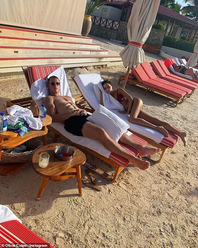 Fun in the sun on the sand: Christina looks at the camera as Olivia poses away on a lounger