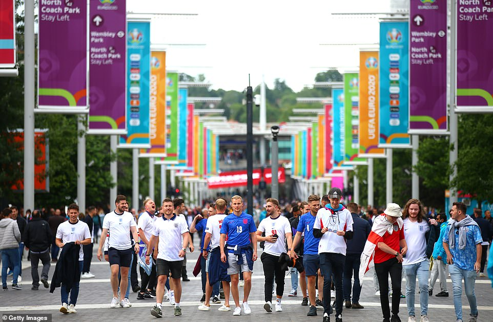 A large group of England fans are seen ambling along Wembley Walk on their way to the stadium, where England play the Czech Republic tonight