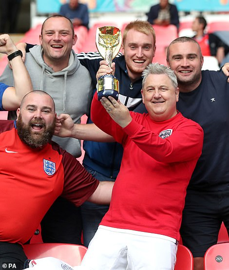 Where have we seen that before? England fans with a replica Jules Rimet trophy at Wembley (pictured left), while other fans wave a Great Britain flag