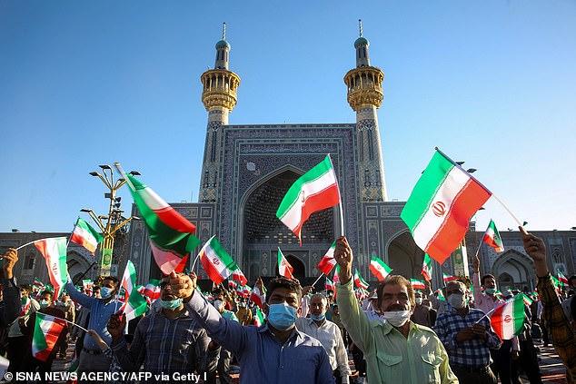 Supporters of Iran's President-elect Ebrahim Raisi cheer at the Imam Reza shrine in the city of Mashhad in northeastern Iran, on June 22