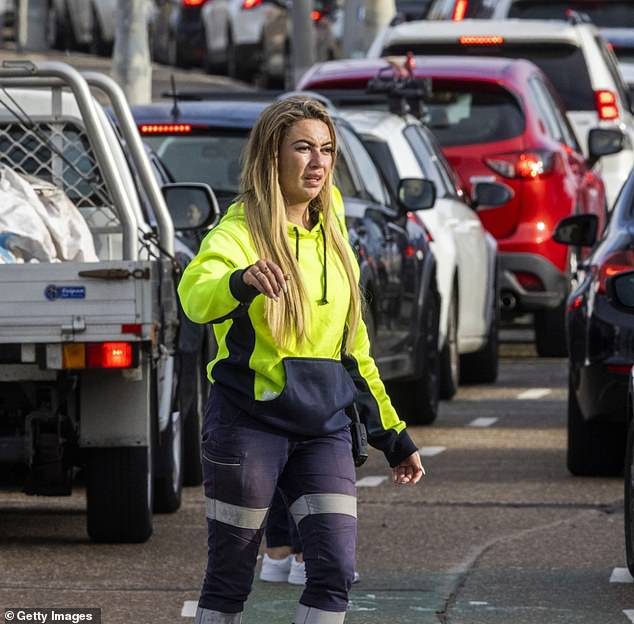 A worker directs traffic along Campbell Parade at the Bondi Beach drive-through Covid-19 Clinic on Wednesday.