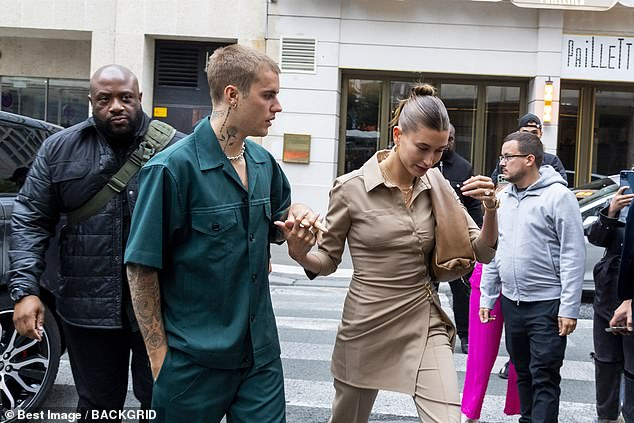 Interlinked:Justin and Hailey took inspiration for each other for their khaki outfits as he looked casual in green baggy clothing while his body art was on show