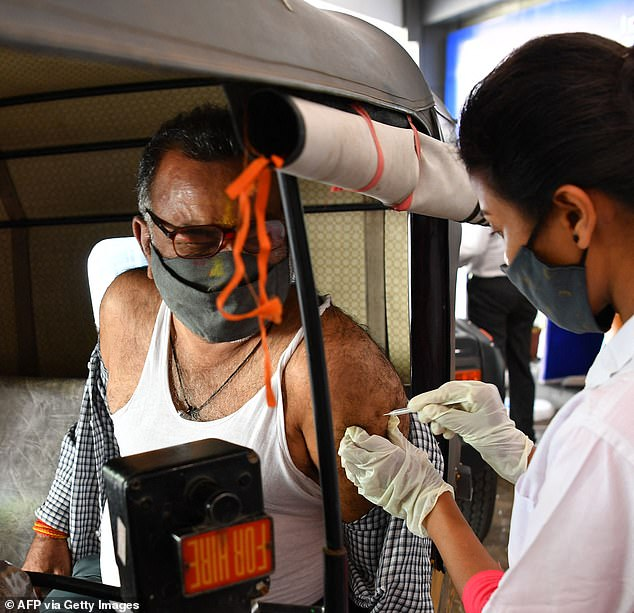 Experts doubt India can maintain its vaccine rollout pace. Pictured: A man is given a jab at a vaccination centre in a Mumbai shopping mall today