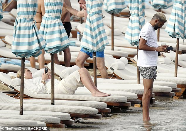 Relaxing: The couple gazed down at their phones as they lay side-by-side on the sun loungers before the football ace cooled off by dipping his feet into the water