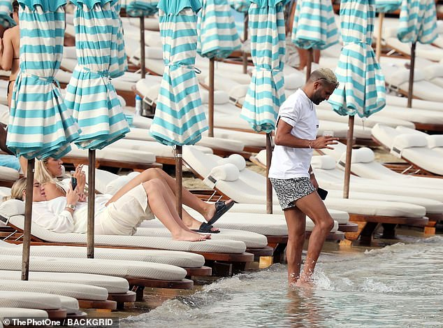 Splashing around: Riyad cooled off as he dipped his feet in the sea