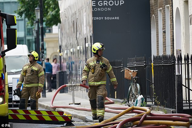 The London fire brigade station commanded said firefighters were doing 'salvage work and trying to prevent water damage on the floors below' (pictured are two men at the scene)