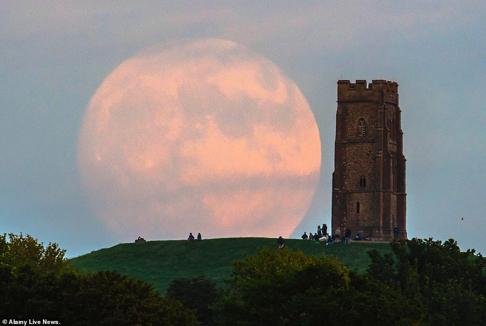 An almost full supermoon was pictured over Glastonbury in Somerset on Wednesday night, ahead of its peak last night