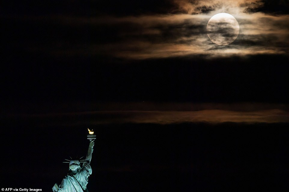 The full moon, known as the strawberry moon, is seen rising behind the Statue of Liberty in New York City on June 24, 2021