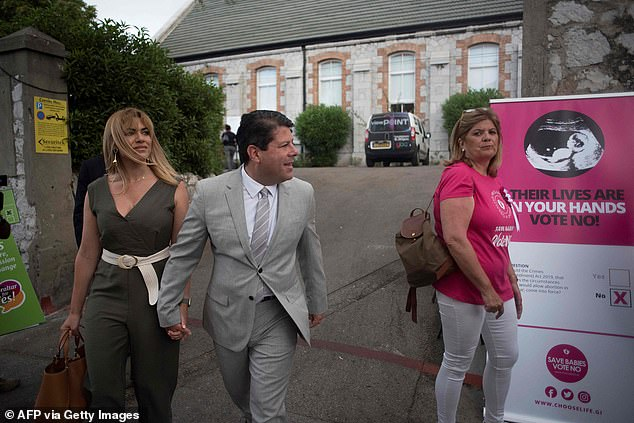 """Chief Minister Fabian Picardo (centre), who had campaigned for a """"yes"""" vote, acknowledged that abortion was """"an emotive subject"""" but hailed the outcome as a necessary step forward. The minister and his wife Justine Olivero (left) leaving a polling station after casting their ballots"""