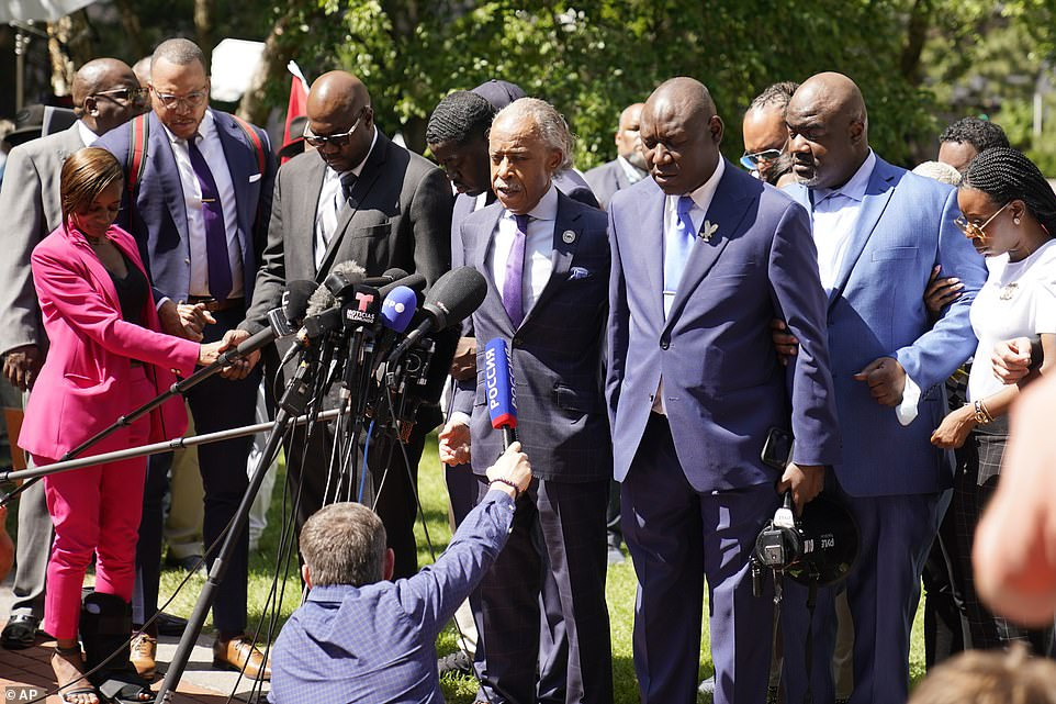 The Rev. Al Sharpton, center, leads George Floyd family members in prayer at a news conference after the sentencing