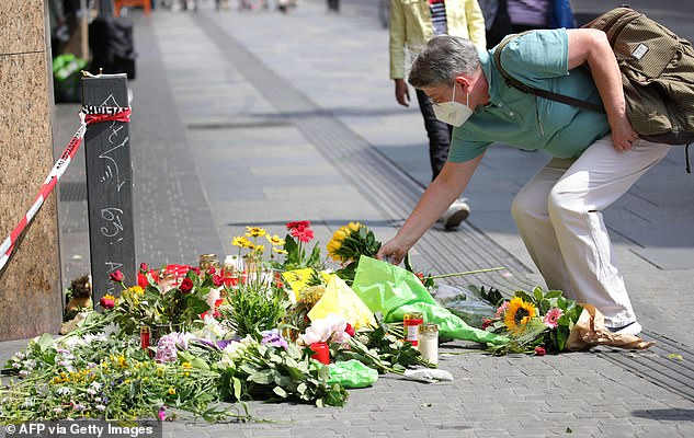 People were seen leaving bouquets of flowers at a makeshift memorial which had been set up on Saturday at the scene in tribute to the victims of the deadly attack