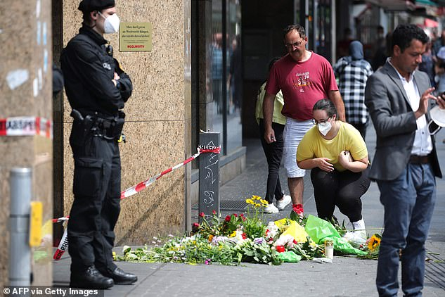 On Saturday, investigators were looking for a motive behind the attack in the German city of Wuerzburg. Pictured: People mourn at a makeshift memorial at the scene of the attack