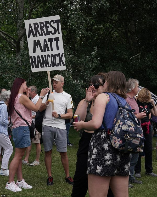 As well as demanding the end to Covid lockdown rules, protesters also brandished placards that demanded police 'arrest Matt Hancock ' after he was caught breaching Covid safety regulations by kissing his married aide