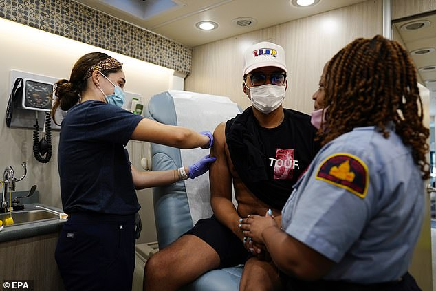 The Pfizer and Moderna vaccines may cause heart inflammation in very rare cases. Pictured: a civilian gets vaccinated at a site in the Navy Yard, Washington, DC