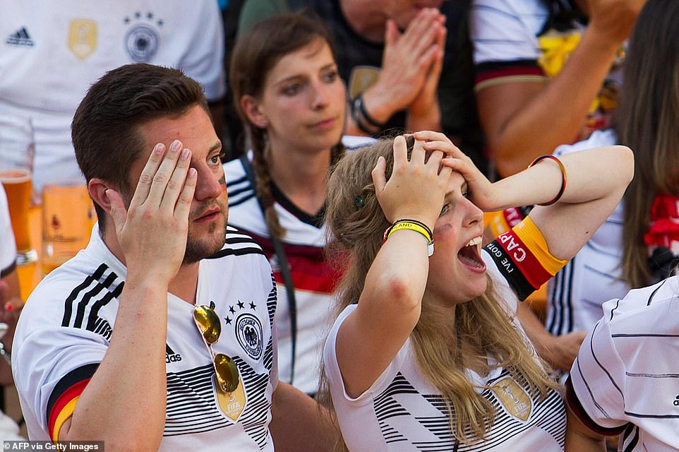 Pictured: German fans are seen with they hands on her head in disbelief as they watched from a pub in Palma de Mallorca.As English newspapers celebrated the Three Lion's 2-0 last-16 Euros victory on Wednesday morning's front pages, the German media struck a very different mood, grieving their team's Wembley defeat and tournament ejection