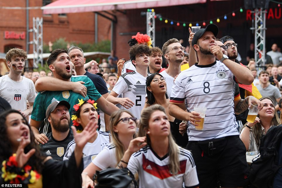 Pictured:German fans react as they watch England vs Germany match on a screen during a public viewing in the courtyard of the Kulturbrauerei, in Berlin, Germany.