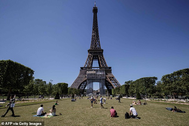 Pictured: People sunbathe in Paris'Champs de Mars park next to the Eiffel Tower. The UK is currently listed as an Orange country by France, meaning that Britons are allowed in with no restrictions if they are fully vaccinated and have a negative Antigen or PCR test result